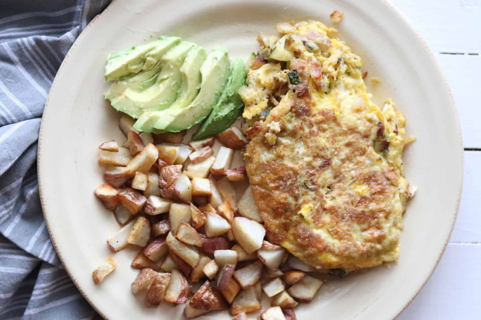 Whole 30 vegetable omelet served with hash browns, avocados, and sauerkraut.
